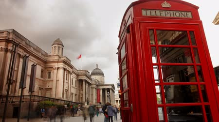 london england : a famous london phone box, with people rushing by, trafalgar square, london Stock Footage