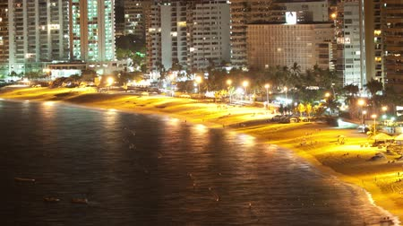felhőkarcoló : timelapse at night of the huge bay of hotels stretching along the coast in acapulco, mexico Stock mozgókép