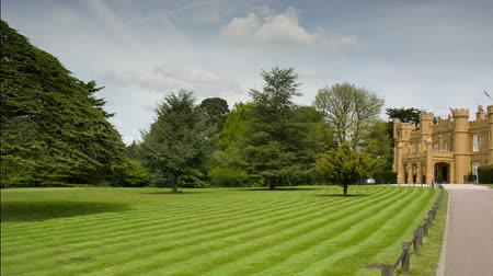 bogaty : panning shot of castle and well manicured garden with lovely tree in england