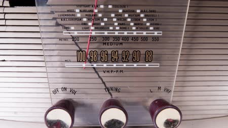 loção : A vintage radio transistor with the dial moving though the different stations and frequencies