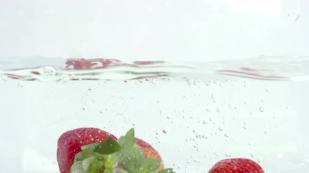 fresh water : fresh strawberry fruit dropped into water shot in super slow motion