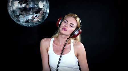 disko : a sexy gogo dancer shot in a studio sitting and posing with a spinning disco ball. Stok Video