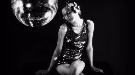discotheque : a sexy gogo dancer shot in a studio sitting and posing with a spinning disco ball. Stock Footage
