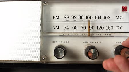 novela : a vintage radio with a hand changing the frequency