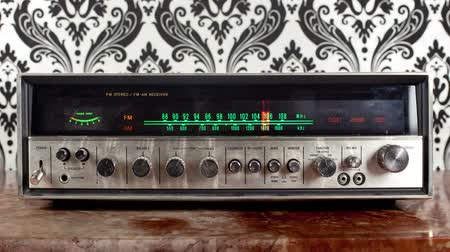 novela : stop motion of a vintage radio receiver with frequency dial moving with a funky wallpaper background