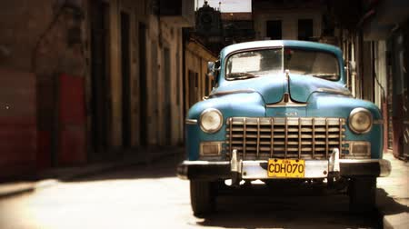 kuba : timelaspe of a classic car in the street with people walking past in havana, cuba