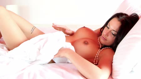 smyslnost : beautiful sexy young woman poses naked on a bed covered with pearls Dostupné videozáznamy