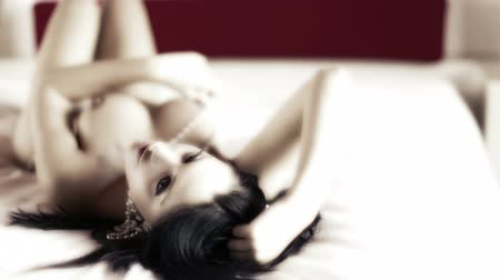 грудь : beautiful sexy young woman poses naked on a bed, covered in pearls
