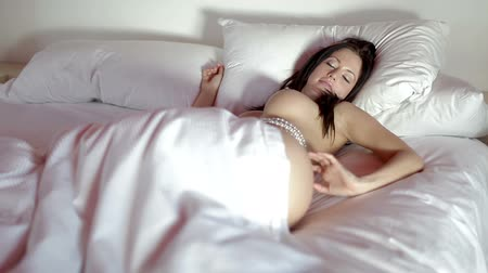 smyslnost : beautiful sexy young woman poses naked on a bed, covered in pearls