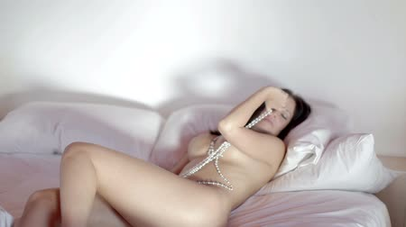эротический : beautiful sexy young woman poses naked on a bed, covered in pearls