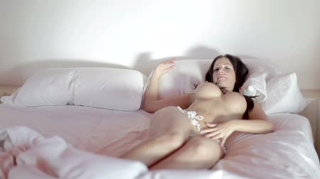 beautiful sexy young woman poses naked on a bed, covered in pearls