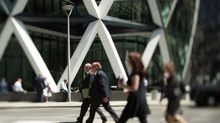 munkahelyek : people walk to work infront of the gherkin building in londons financial district