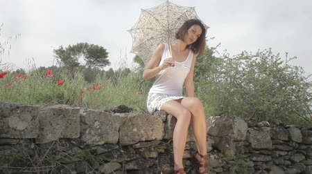 pasture land : a beautiful young woman outdoors in the countryside relaxing with a parasol
