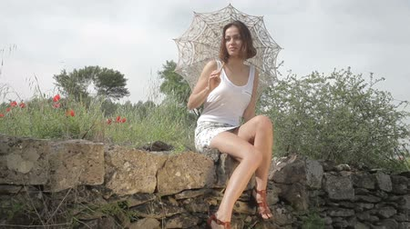çevre : a beautiful young woman outdoors in the countryside relaxing with a parasol