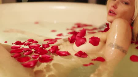 piersi : A sexy beautiful woman in a large hotel bath filled with rose petals