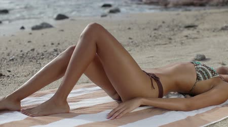ciało : Beautiful girl in a bikini sunbaths on the beach at sunrise, baja california sur, mexico Wideo