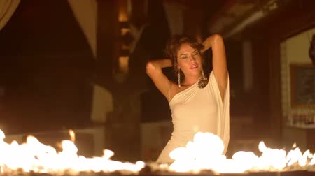 after fire : Beautiful sexy woman dances infront of a fire Stock Footage