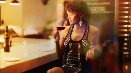 Beautiful sexy woman drinks wine in a hotel bar at night