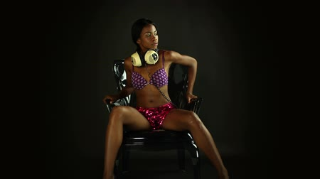 Sexy young woman sits in stylish chair listening to music on headphones