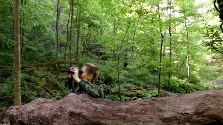guerrilla : Young woman in camouflage clothes with binoculars in the forest. Stock Footage