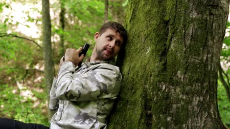 guerrilla : A man shoots a pistol in the forest.