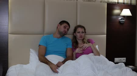 spolu : A man and a woman are watching TV on the bed. Bored in front of TV. Dostupné videozáznamy
