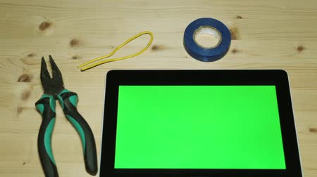 alicate : A hand tool and a tablet with a green screen for your content. Stock Footage