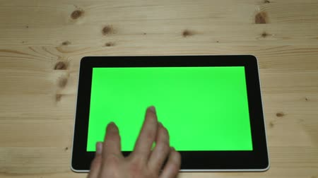 ремонт : Tablet computer with a green screen on the background of a wooden table.