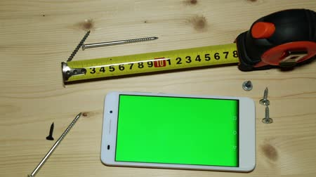 ruletka : A smartphone with a green display, a construction tape measure and screws.