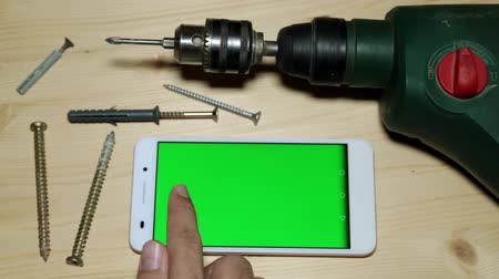 parafusos : Electro drill and smartphone with a green screen.