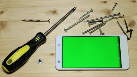 csavarhúzó : Screwdriver, screws and smartphone with a green display.