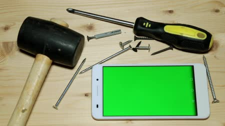csavarhúzó : Building tools and a smartphone with a green screen. Stock mozgókép
