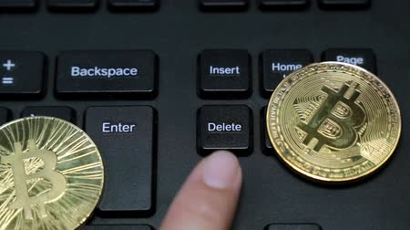 excluir : Coins bitcoin, finger presses the delete key on the keyboard. Stock Footage