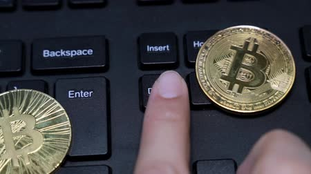 отпечаток пальца : Coins bitcoin, a person presses the delete key on the keyboard.