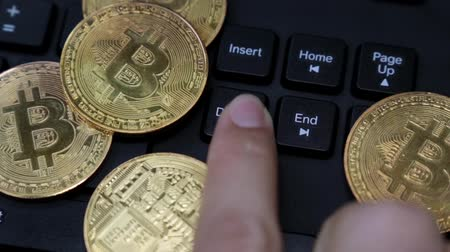 отпечаток пальца : Gold coins bitcoin, a person presses the delete key on the keyboard.