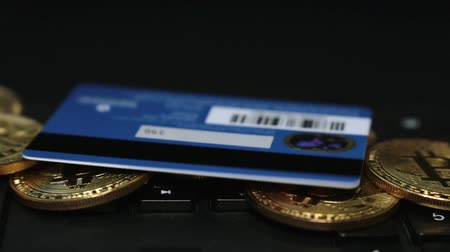 buy gold : Gold coins bitcoins and bank card on the keyboard.
