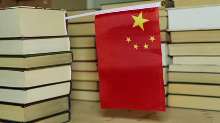 воспитание : Flag of China and paper books. Chinese flag on the background of books. Стоковые видеозаписи