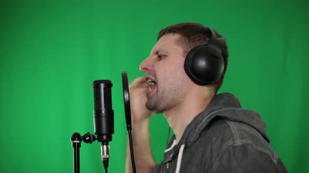microphone : The man sings and reads the rap into the microphone. Rapper, singer on a green background. Stock Footage