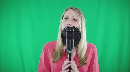 караоке : A young woman sings into a microphone on a green background. Стоковые видеозаписи