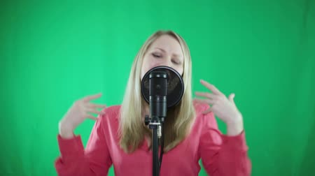 vocalist : A woman sings into a microphone on a green background.