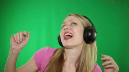 microphone : A woman is dancing and listening to music on headphones on a green background.