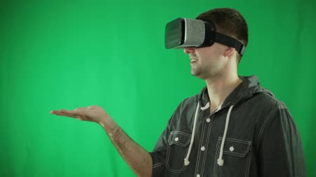interativo : A person in virtual reality glasses is holding his palm up.
