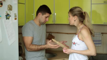 quarreling : A man and a woman are arguing in the kitchen. Family quarrel, conflict.