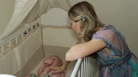 bottle feeding : Woman and child in a cot. Mom and baby in the childrens room.