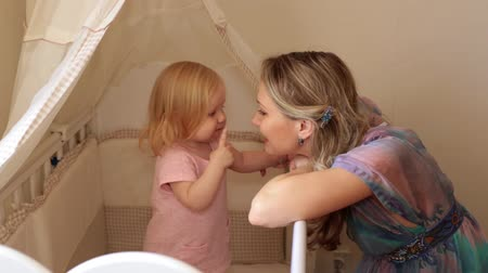 cradle : Mom and baby in the childrens room. A woman with a small child at home. Stock Footage