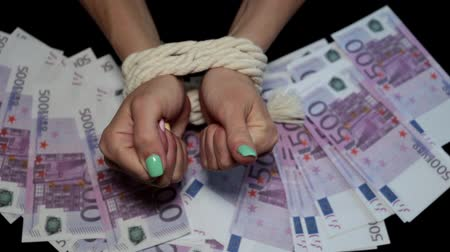 kötés : Womens bound hands against the background of money Stock mozgókép