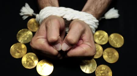 kötés : Bitcoins and bound hands of a person. Financial slavery, excitement, debts.