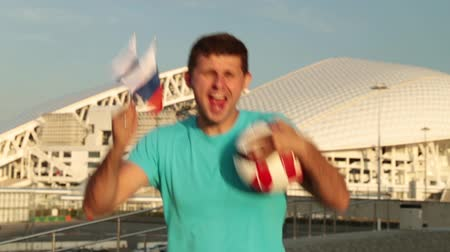 fisht : A man is a football fan with a Russian flag in the background of the stadium.
