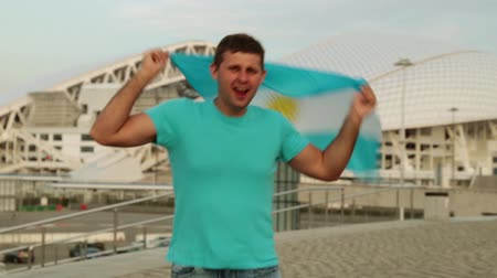 fisht : man is a fan with the flag of Argentina.