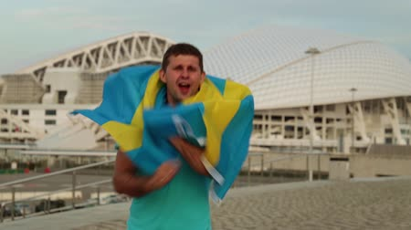 İsveççe : man is a fan with the flag of Sweden.